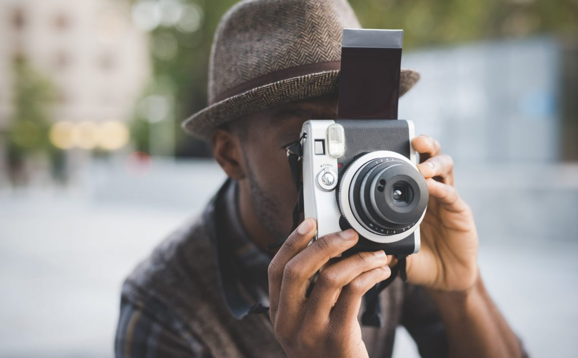 Half length of young beautiful afro black man outdoor in the city holding instant camera, shooting - photography, creative, artist concept