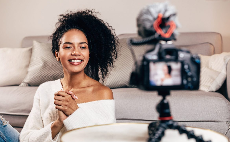 Happy female vlogger live streaming from living room using dslr camera