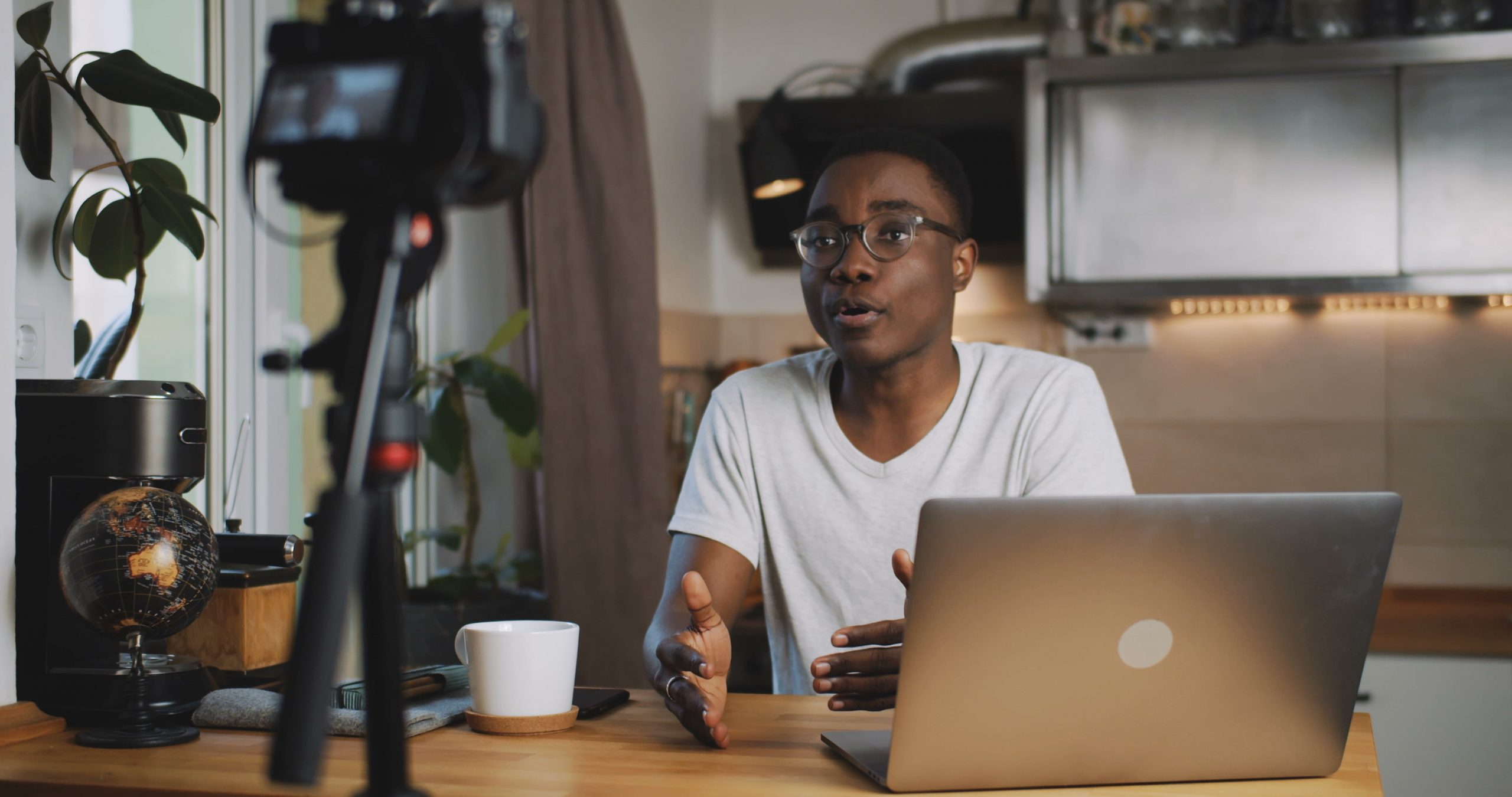 Happy young smart black blogger man filming new vlog video with professional camera in kitchen at home slow motion. Blogging, live streaming and entertainment as modern creative freelance work.